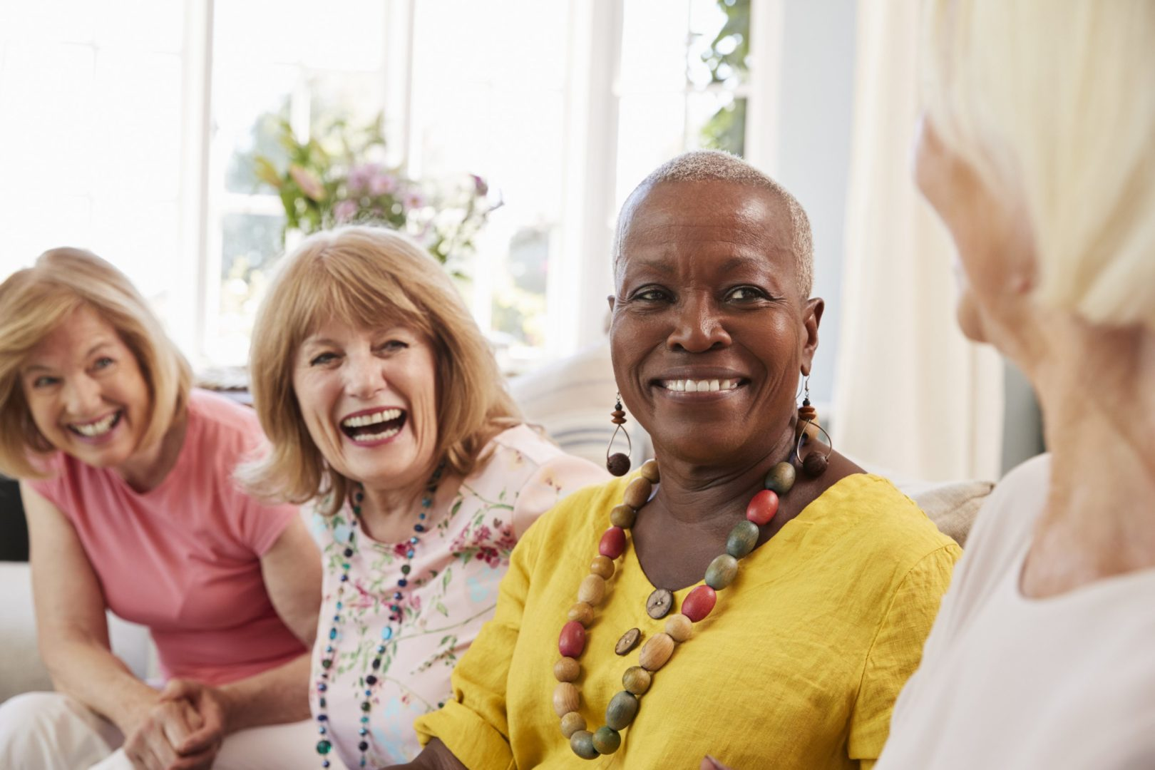 Four senior female friends, connecting over a good story and laughing. From left to right - Caucasian woman with shoulder length blond hair, wearing a pink t-shirt and stone colored pants, big smile on her face. Caucasian woman with shoulder length light brown hair, laughing, wearing a flowery blouse and long beaded necklace. African American woman with short gray hair, wearing a yellow linen blouse and beaded earrings and necklace. Caucasian woman with bob length blond hair and light pink top.
