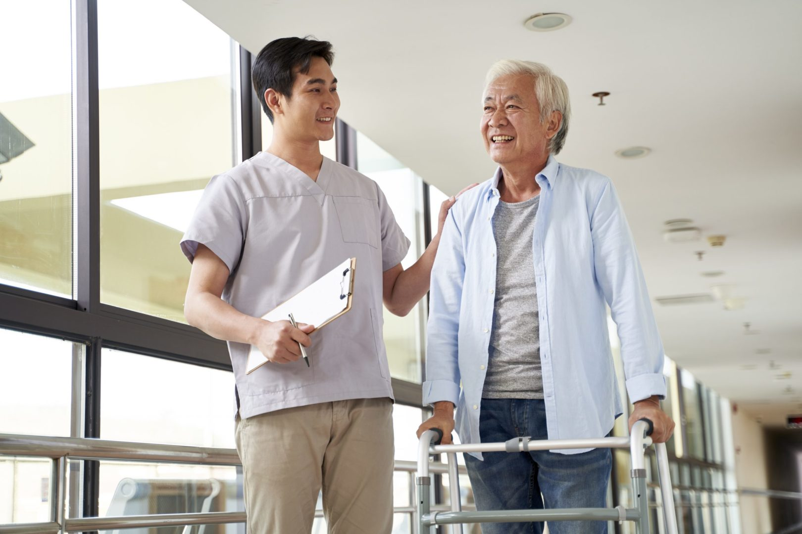 Happy senior asian man talking with a physical therapist in rehab center. The therapist, on the left, is wearing medical scrubs and holding a clipboard and pen. The man on the right has a walker and is wearing a gray t-shirt with a light blue button down open to the front, as well as blue jeans. The setting is a rehab center.