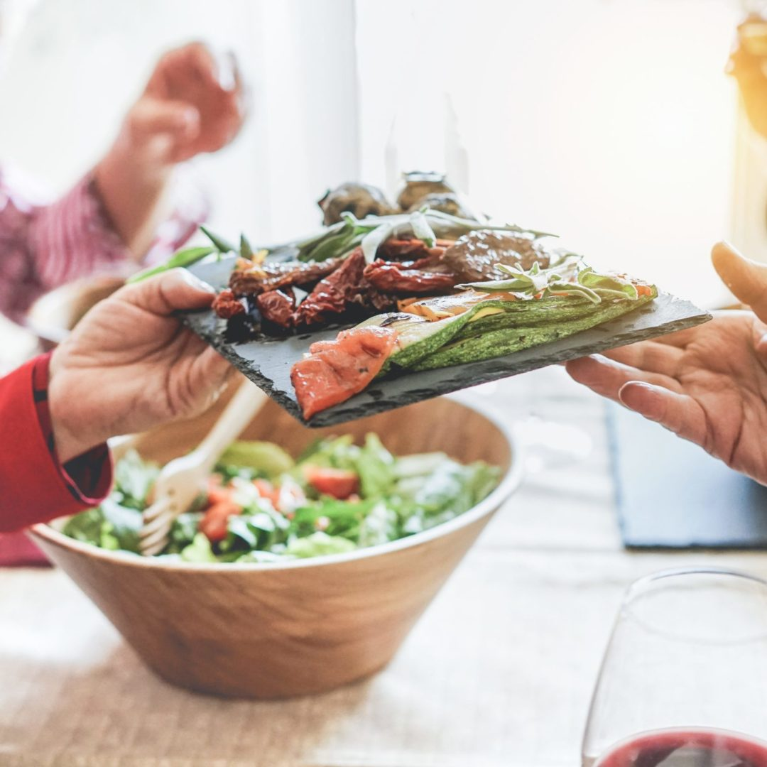 Senior people having a vegan lunch together. Photo shows hands passing a plate of vegetables from left to right. Plate includes roasted zucchini, tomatoes and salad. The person on the left is wearing a long-sleeved red jacket. In the background is a large salad bowl with salad. In the foreground is a glass of red wine.