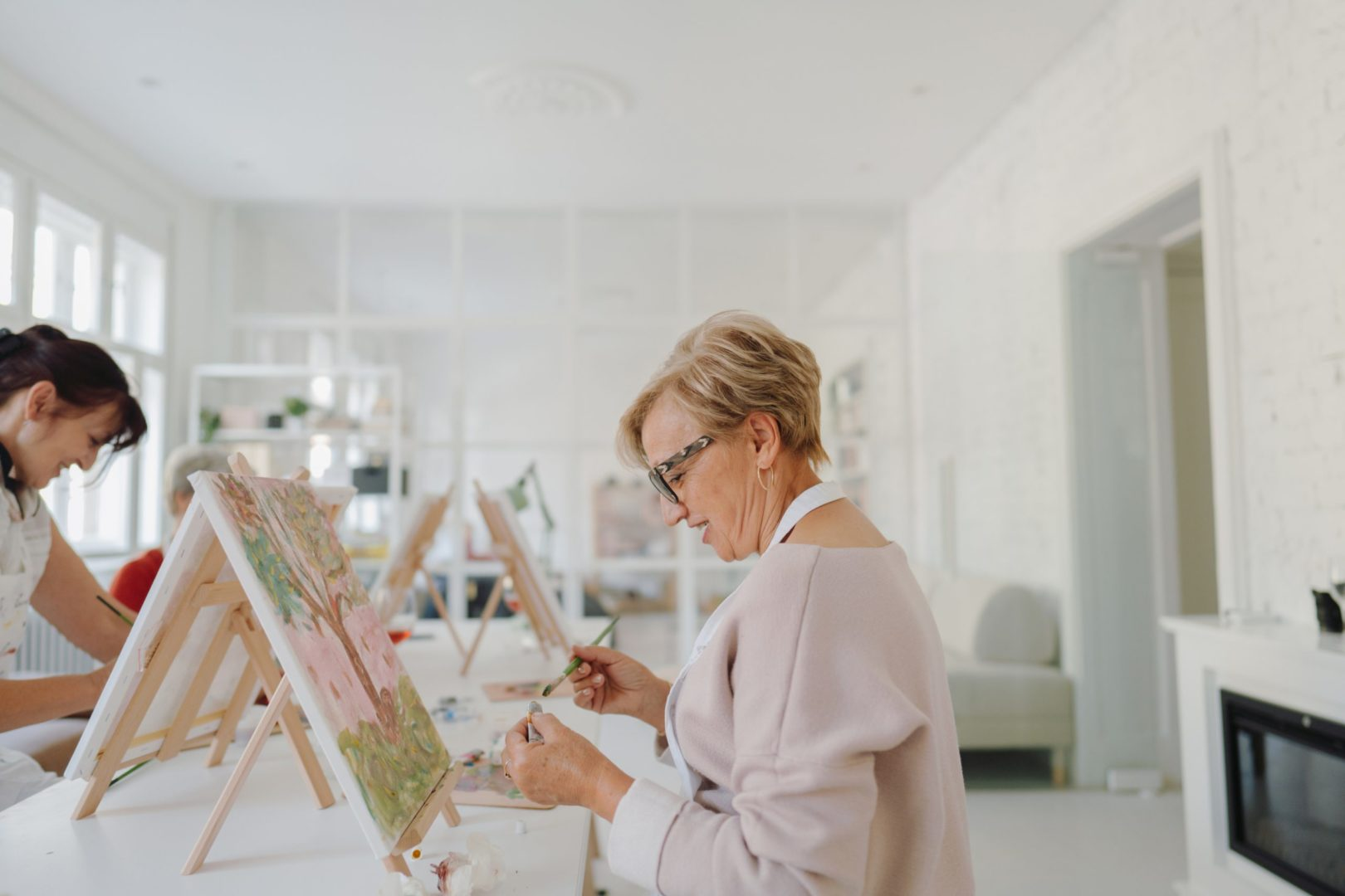 Photo of a senior woman taking painting classes with her friends in an art studio; connecting with her friends and learning how to paint together. Woman is wearing a light pink sweater and white smock. She is painting a tree with leaves and grass under it.