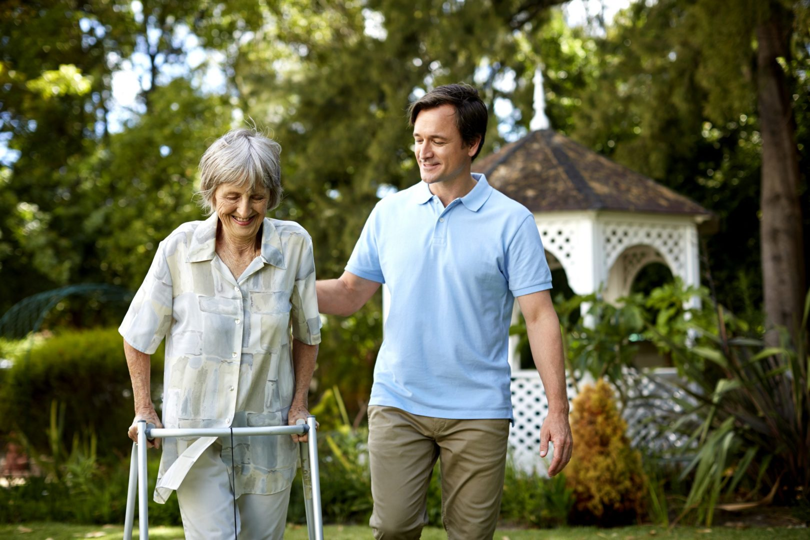 Adult son assisting mom with walker at nearby park