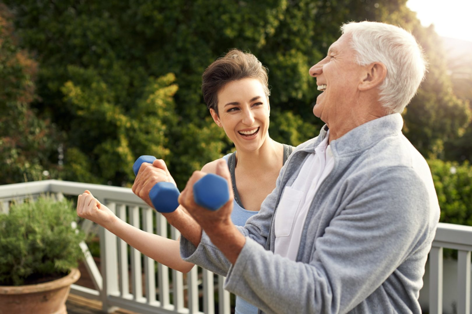 Cropped photo of a senior man working out with a female instructor at home