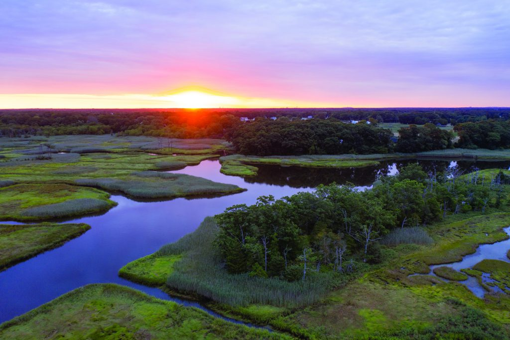 Forests and streams surround Anchor Bay at East Providence. Photo taken at sunset, with the sun dipping behind the horizon to create yellow, pink, purple and blue effect in sky.