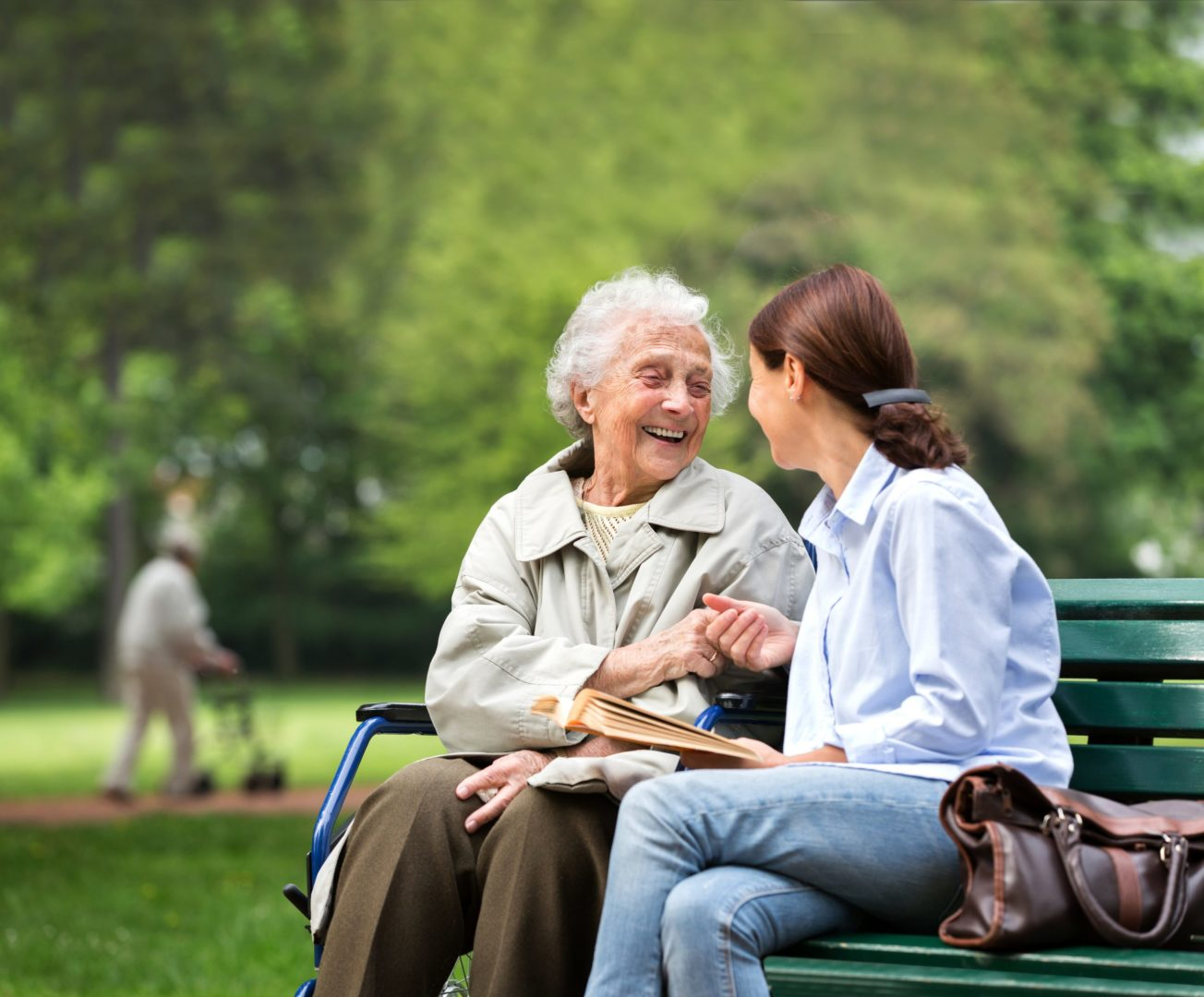 A photo of two people sitting on a bench.