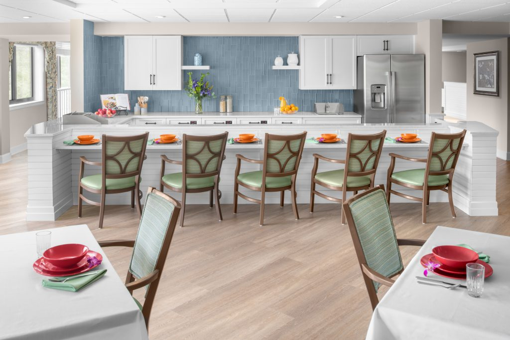 Open dining space for residents and families to connect over a meal. Space is open and bright with white woodwork and blue tile accents. There are settings for five guests at a bar-style seating area with chairs. In the foreground are two tables with seats, set with red dishware.