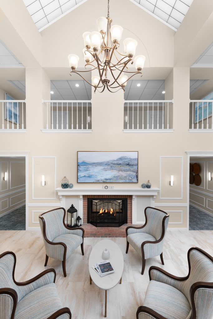 Front lobby and sitting area with four wing-backed chairs in front of a fireplace with warm fire. Four chairs surround a white, oval-shaped coffee table that holds two books and a white vase. The large fireplace mantle holds blue decorative glass jars and there is a large painting of blue mountains and water hanging above. The floor is beautiful large cream tiles. The space is open and bright. There is a large chandelier hanging from the glass atrium ceiling. The chandelier holds ten sconces with bright light coming from each. Above the lobby is an open balcony with a white railing.