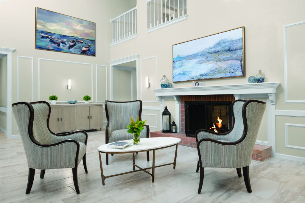 Front lobby and sitting area with three wing-backed chairs in front of a fireplace with warm fire. Three chairs surround a white, oval-shaped coffee table that holds two books and a vase with yellow flowers. The large fireplace mantle holds blue decorative glass jars and there is a large painting of blue mountains and water hanging above. On the far wall is a buffet-style storage cabinet with plants and a glass blue bowl. Above, on the wall, is a large painting of water with six unmanned row boats. The floor is beautiful large cream tiles. The space is open and bright.