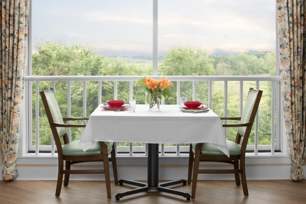 Dining room, table for two set with a white tablecloth, red dishware and a case with orange lillies. Two chairs with light green fabric and dark wood on the left and right of the table. The table is set in front of a large window with a gorgeous view of a lush, green forest. The window is planked by floral drapes.