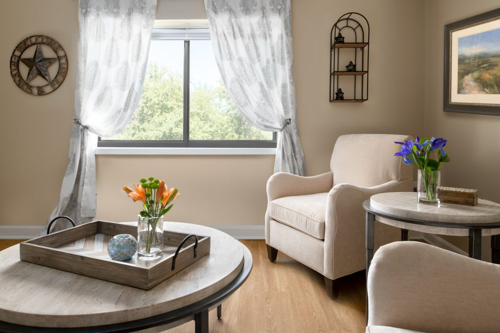 Spacious seating area with a white coffee table on the left and two cream chairs on the right. The coffee table holds a tray with flowers and a candle. There is a large window with soft white curtains.