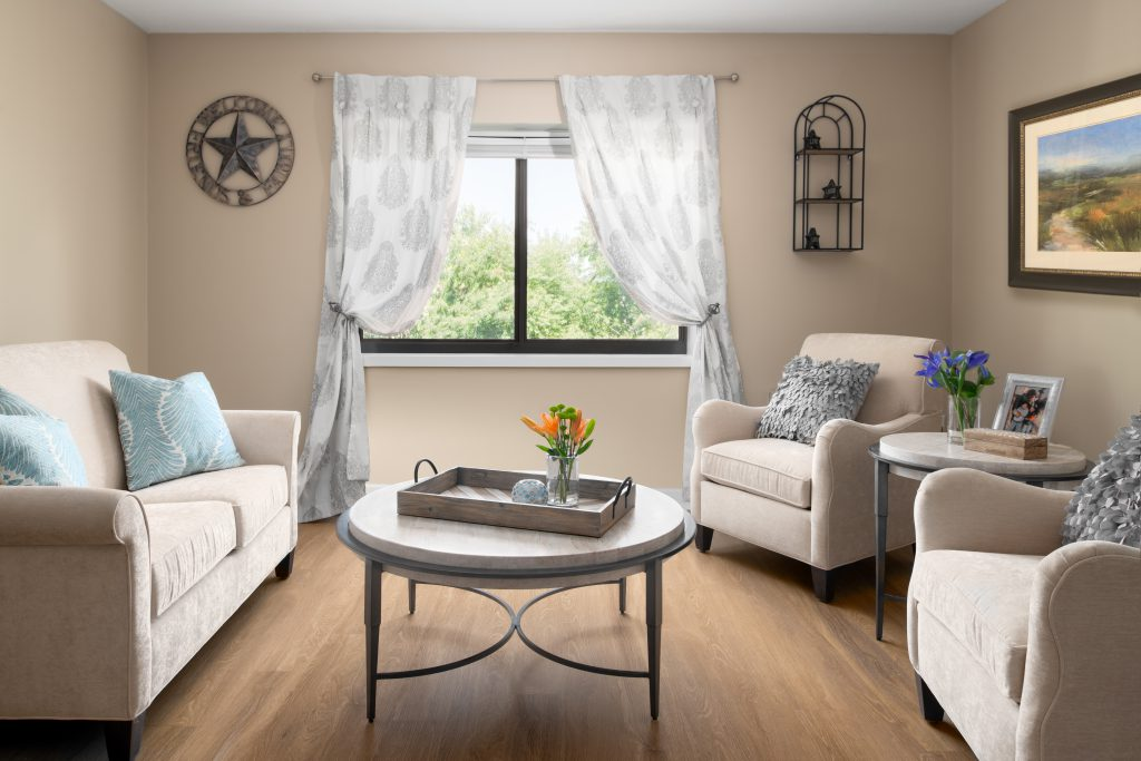 Spacious seating area with a cream sofa to the left, white coffee table in the middle and two cream chairs on the right. The coffee table holds a tray with flowers and a candle. There is a large window with soft white curtains.