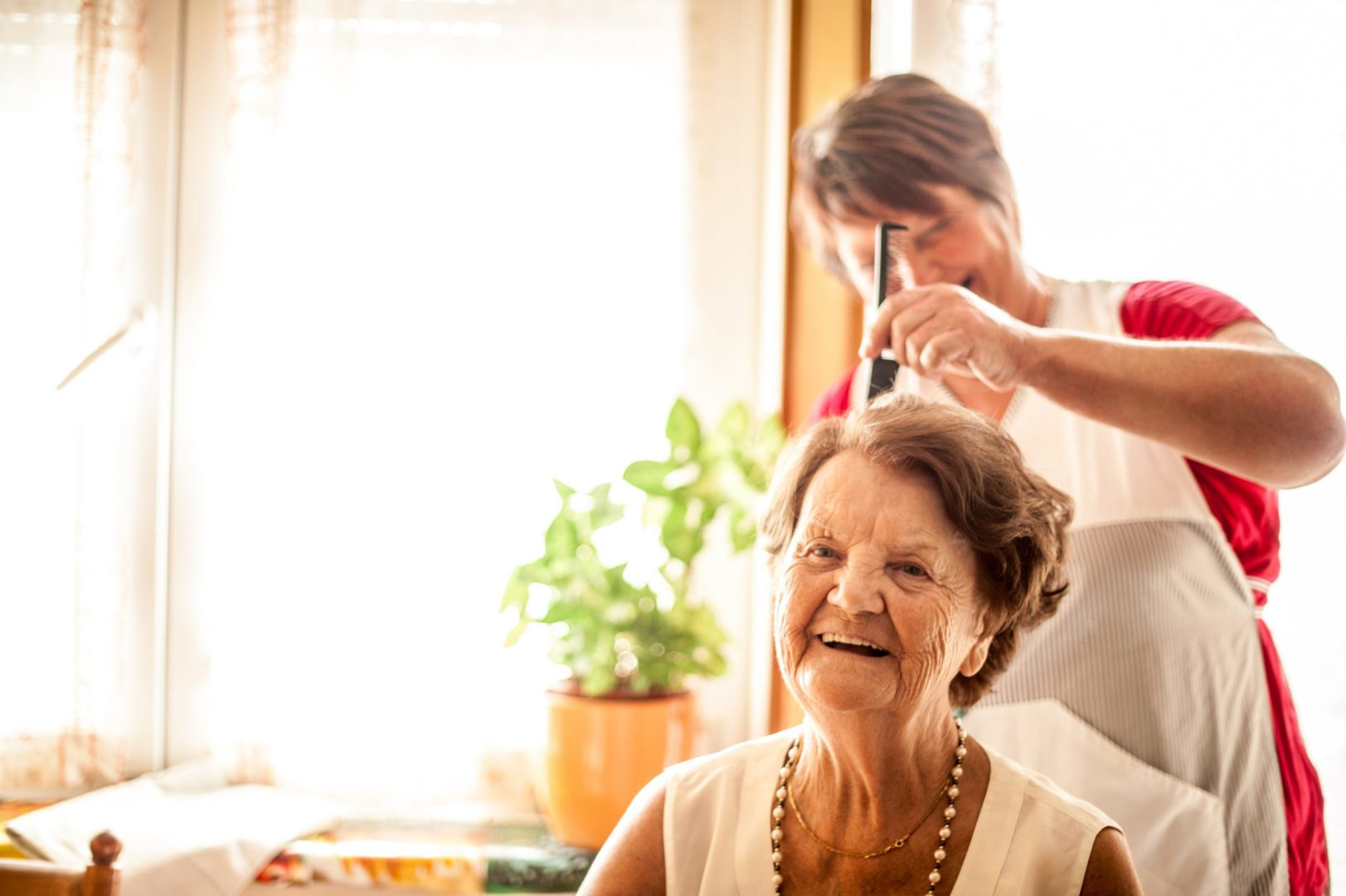 Caucasian senior woman has her hair styled. She is sitting in the foreground with the stylist to the back of her. She has short brown, wavy hair and is wearing a sleeveless, light cream linen top, a pearl necklace and short gold necklace. She is smiling. The stylist is behind her with a comb and is wearing a red top and apron. She has short brown hair. In the background is a large window and plant in a yellow pot.